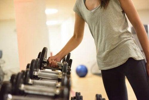 kobieta biorąca hantlę - odchudzanie z treningiem siłowym