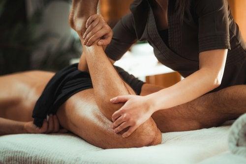 Fizjoterapeuta rozciągający nogi pacjenta - kontuzja ścięgna