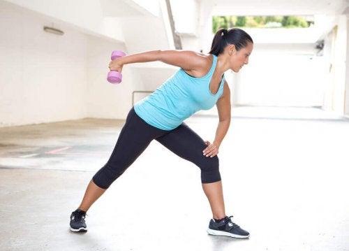 powrót na siłownię - kobieta robi ćwiczenia z małym ciężarem
