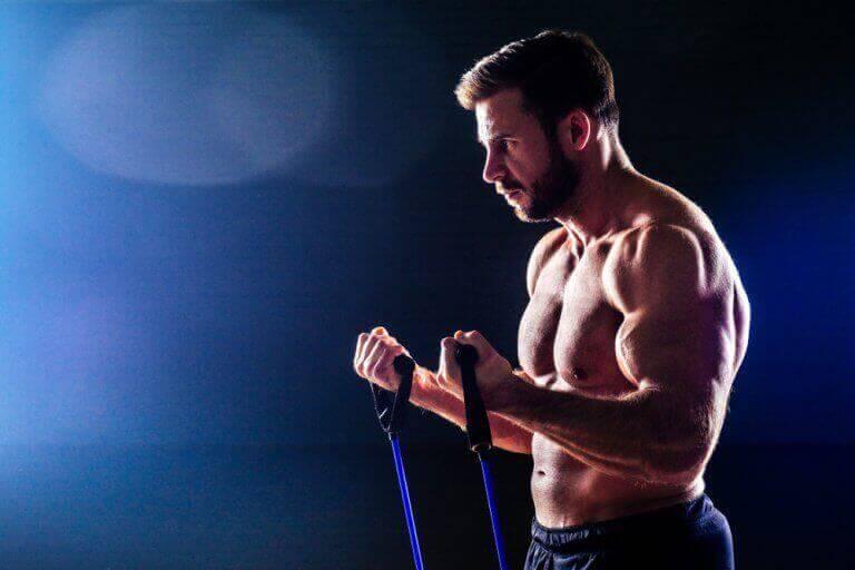 Mężczyzna ćwiczący biceps z gumami - łatwe ćwiczenia ramion