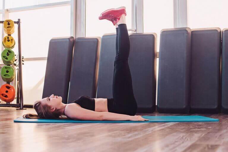 dziewczyna robi podnoszenie nóg na ćwiczenie brzucha