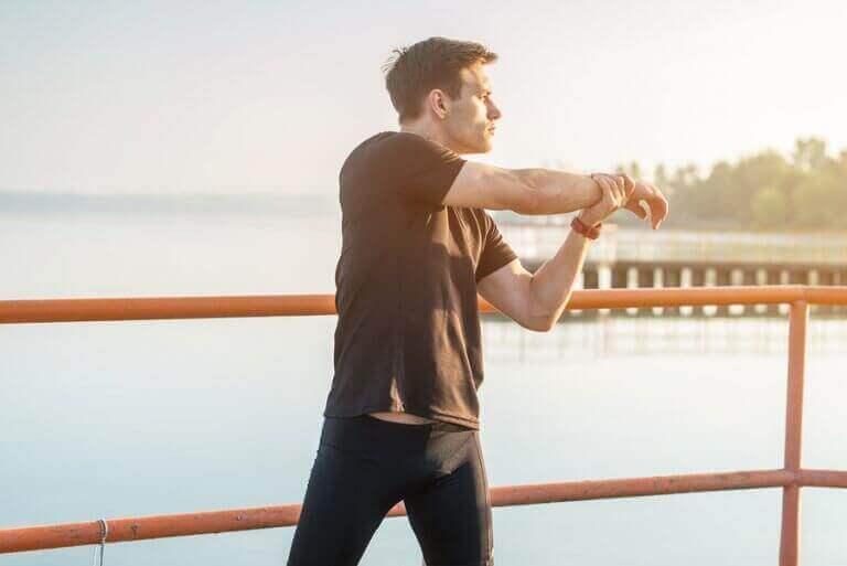 Mężczyzna robi ćwiczenia rozciągające ramiona - najczęściej występujące kontuzje