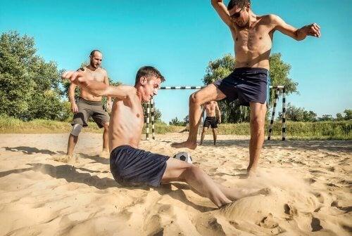 chłopcy grają w plażowy football - sporty plażowe