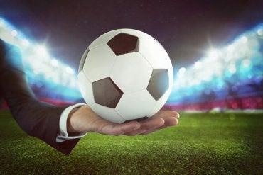 mężczyzna trzyma piłkę nożną