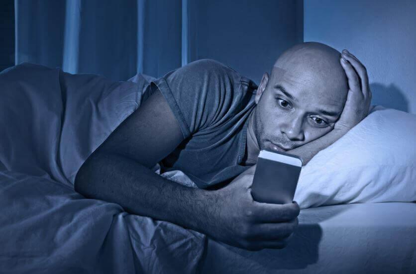 Mężczyzna z telefonem w łóżku