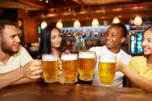 Picie alkoholu w pubie, kufle z piwem