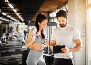 Kobieta z trenerem w siłowni planuje trening aby zapobieganie kontuzjom