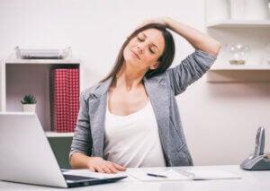 Kobieta rozciąga mięśnie szyi, aby leczyć bruksizm