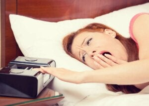 Zaspana kobieta wyłącza budzik a jet lag