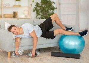 Wykończony mężczyzna po treningu śpi na kanapie a jet lag