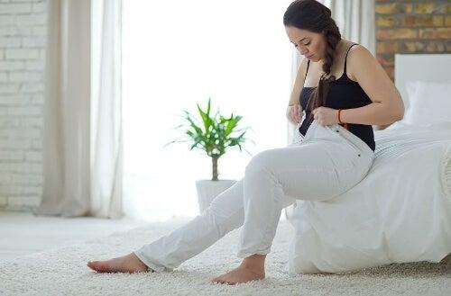 Kobieta siedzi na sofie w za dużych spodniach