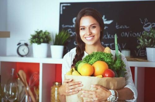 Kobieta trzyma worek z warzywami i owocami