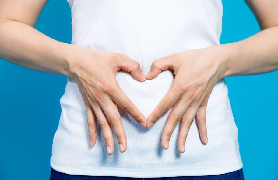 Mulher fazendo um coração na frente da barriga