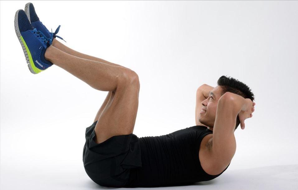 Homem fazendo abdominal com as pernas elevadas