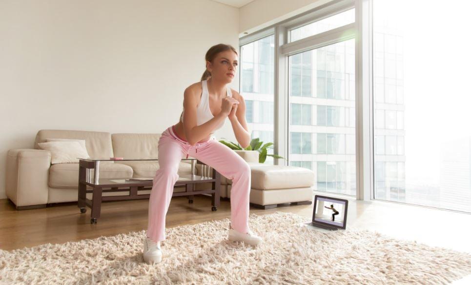 Mulher fazendo agachamento na sala de casa seguindo treino no computador