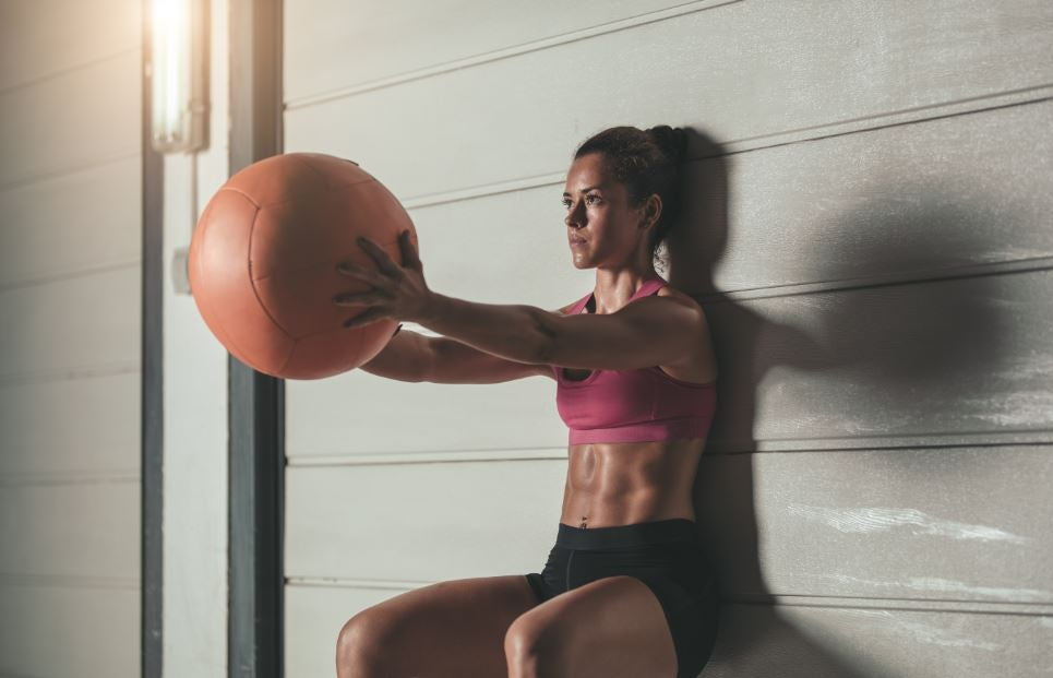 Mulher fazendo agachamento isométrico com bola