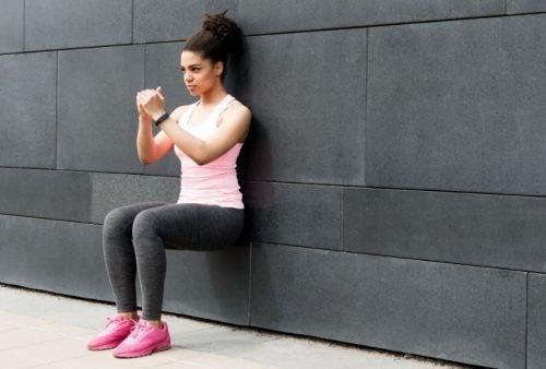 Menina fazendo agachamento isométrico encostada em uma parede