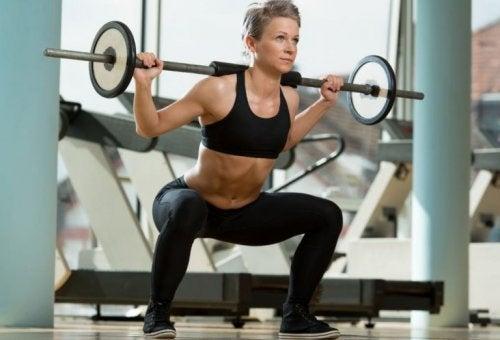 Mulher fazendo agachamentos com peso
