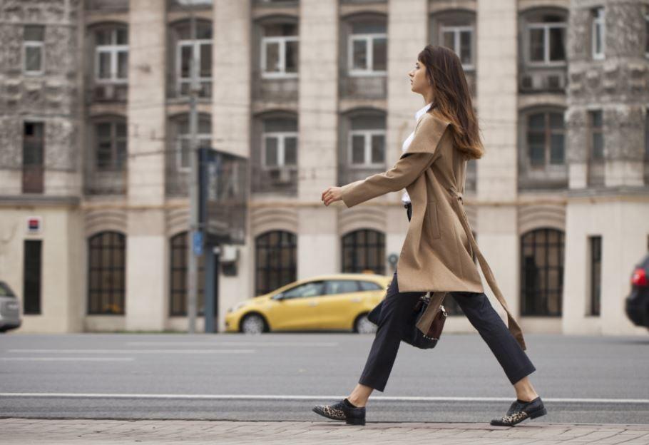 Mulher caminhando na cidade com postura flexionada