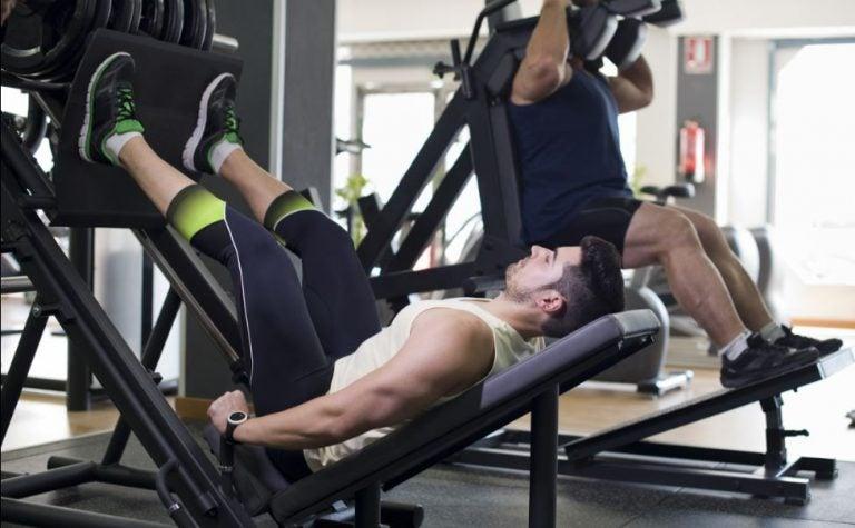Homem fazendo leg press na academia