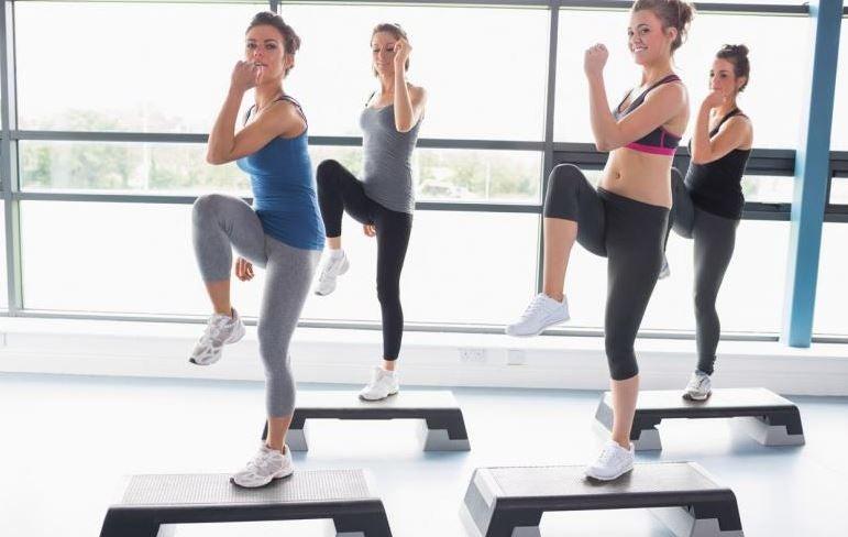 Mulheres fazendo uma aula de step na academia