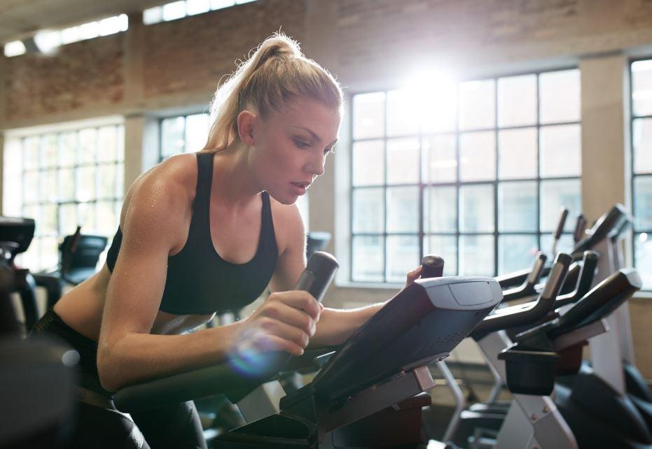 Mulher praticando spinning sozinha em uma academia