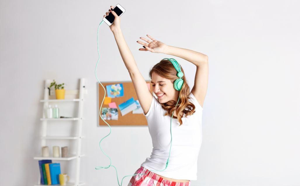 Menina dançando com ipod em casa