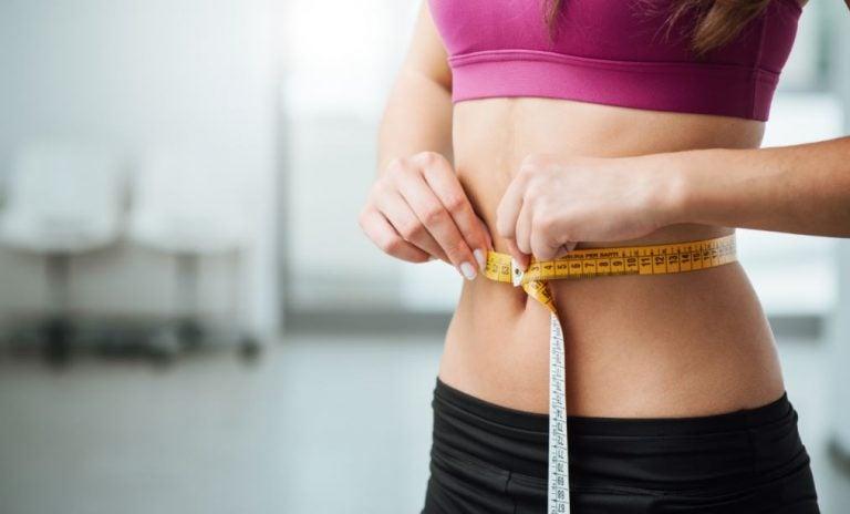mulher medindo a cintura com uma fita métrica