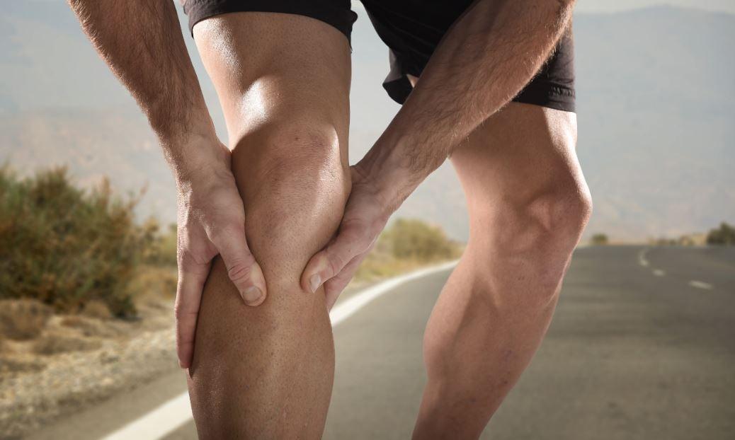homem com mão no joelho sentindo dor
