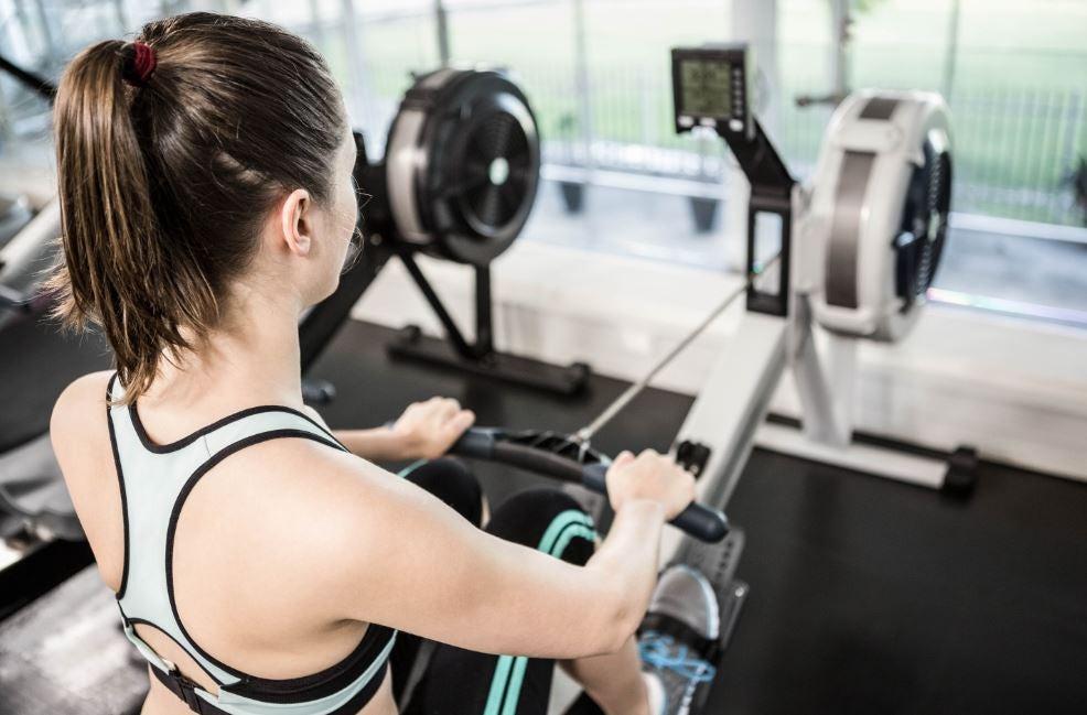 Mulher fazendo exercício na máquina de remo na academia
