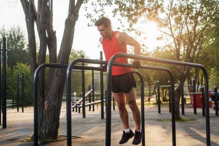 Homem fazendo tríceps nas barras paralelas de um parque