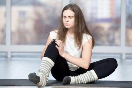 Menina com dor no joelho na academia