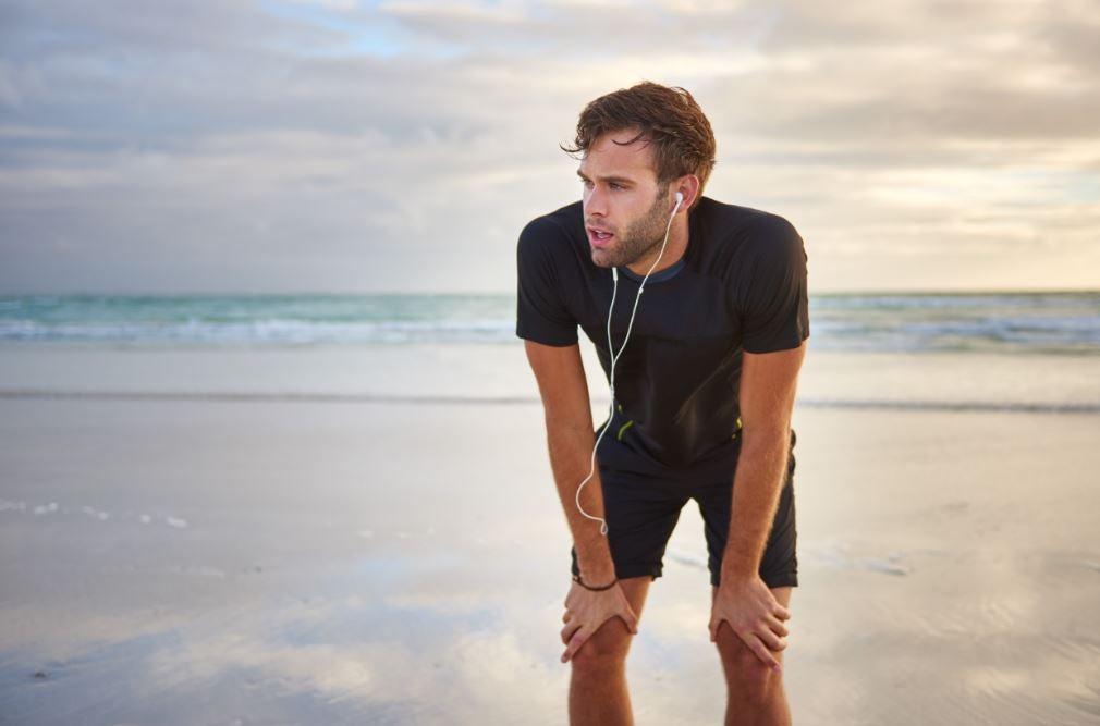 Homem correndo na praia suado e cansado