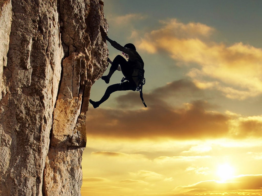 Homem fazendo escalada ao por do sol