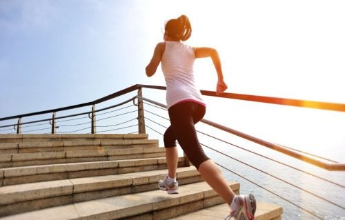 Mulher se exercitando subindo escadas correndo
