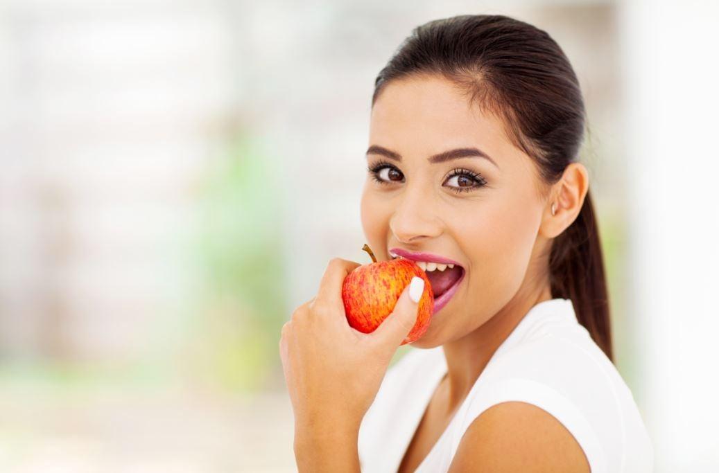 Mulher comendo uma maçã