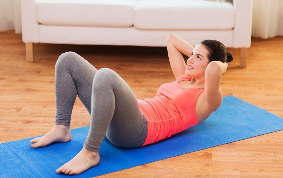 Mulher fazendo abdominais na sua sala