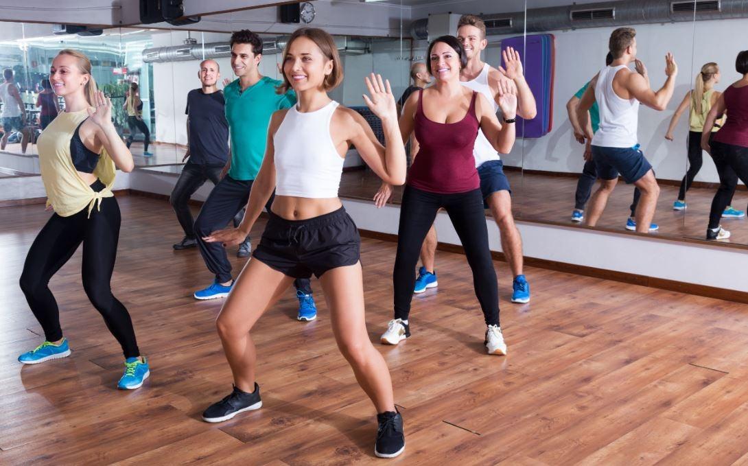 Alunos dançando zumba em uma aula de academia