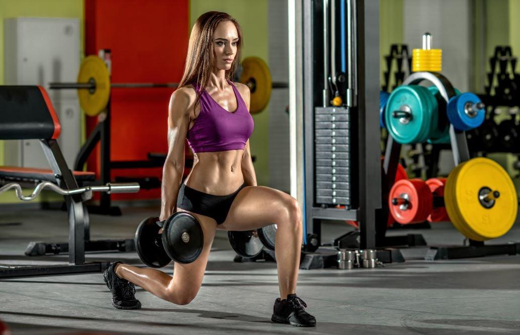 Mulher fazendo passada na academia com pesos