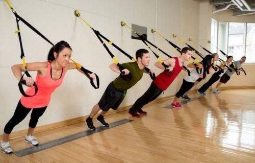 Alunos fazendo treino de musculação no TRX