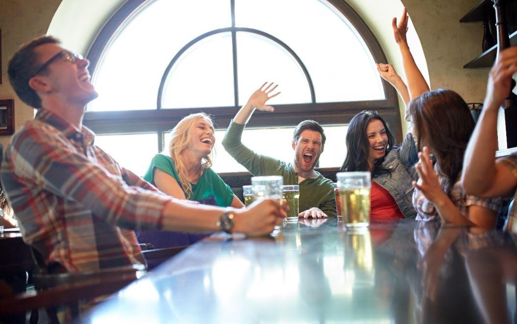 Amigos bebendo no bar, animados e rindo