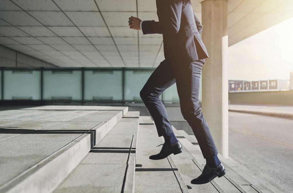 Homem subindo as escadas para o trabalho correndo