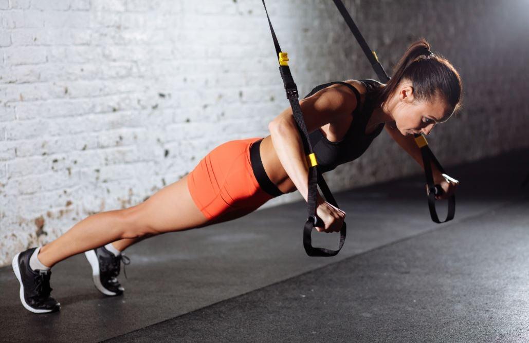 Mulher fazendo exercícios no TRX na academia