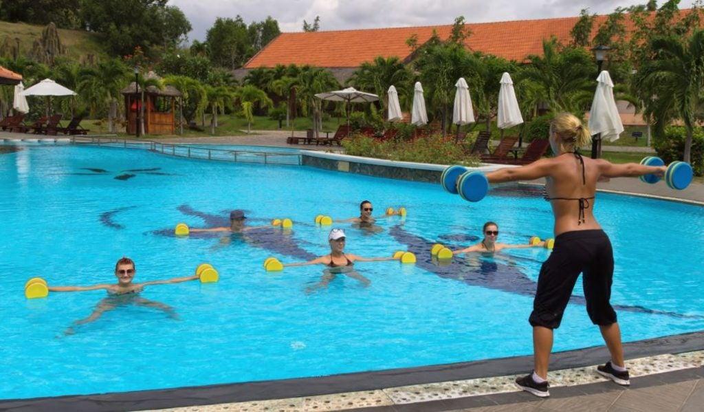 Pessoas fazendo hidroginástica em uma piscina de hotel