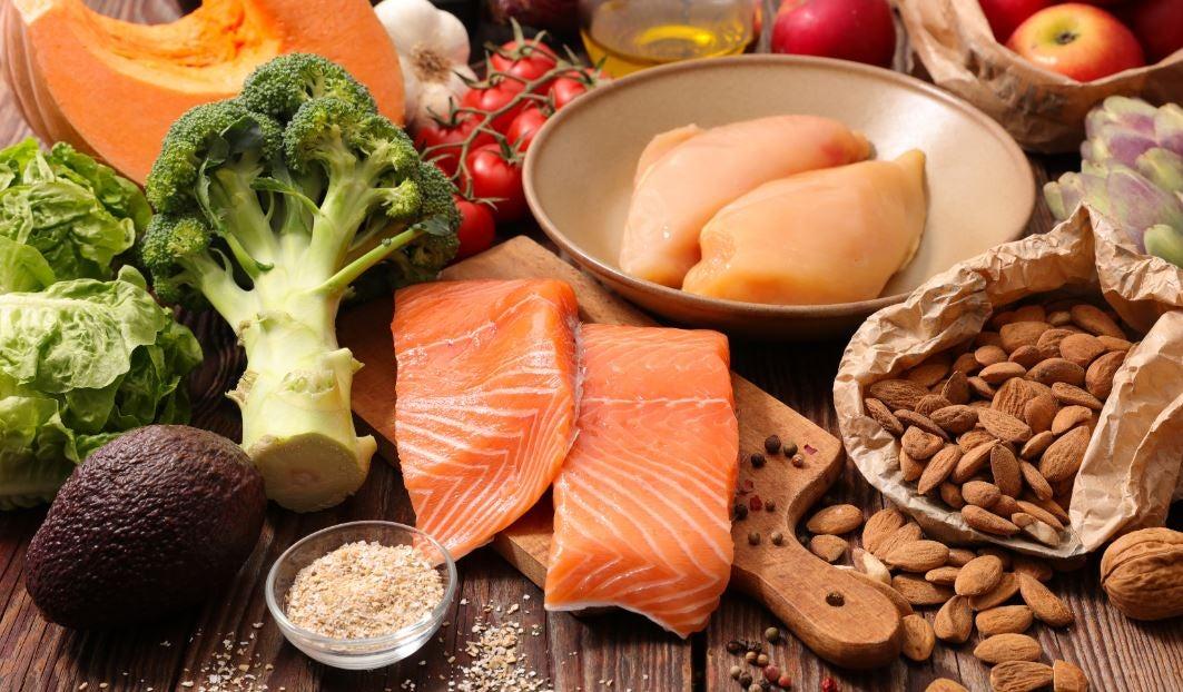Vários alimentos saudáveis como salmão, peixe, brócolis, amêndoas, abacate, tomate, alface, abóbora...