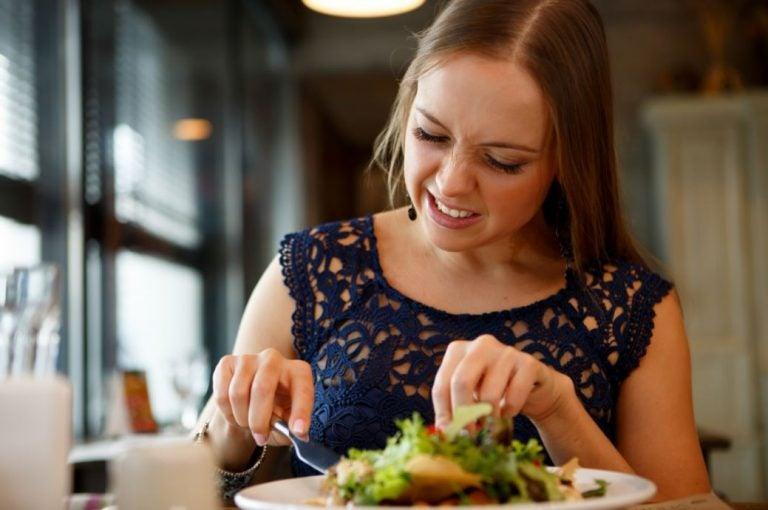 Mulher comendo uma salada não muito feliz