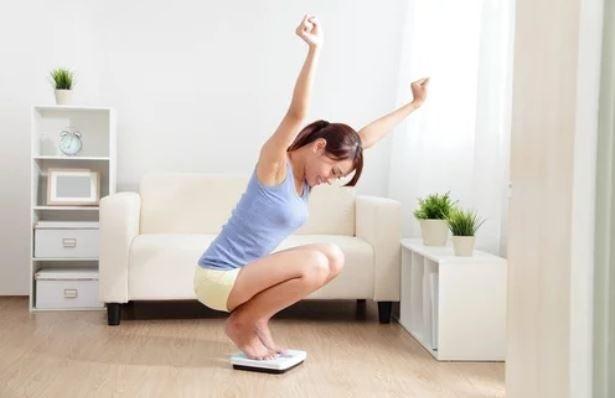Mulher se pesando feliz porque perdeu peso