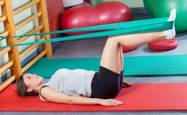 Mulher fazendo exercícios com elástico para as pernas