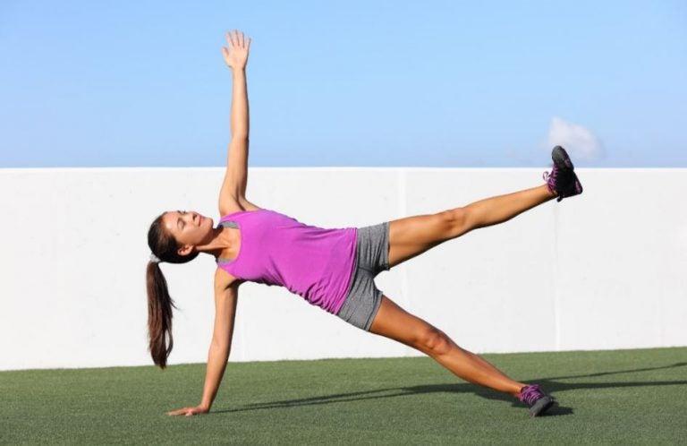 Mulher fazendo o exercício de prancha lateral