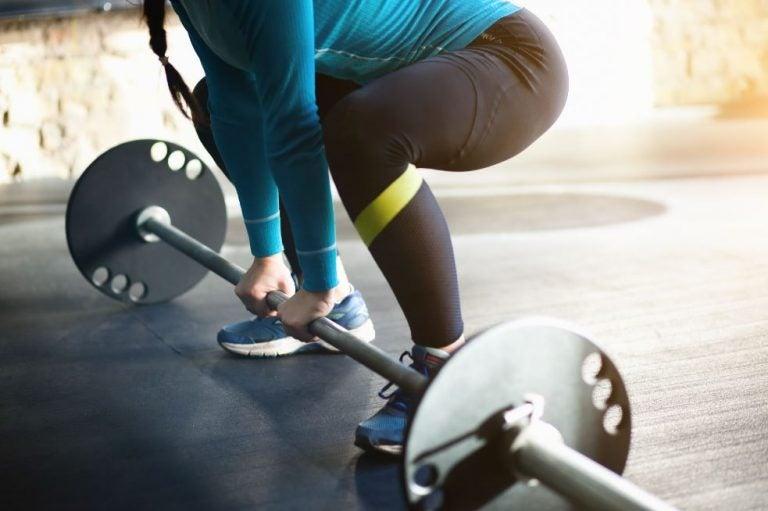 Mulher fazendo o levantamento terra na academia com pesos
